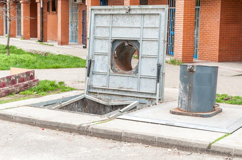 Open cover of an underground garbage container on the street in the city.  royalty free stock photography