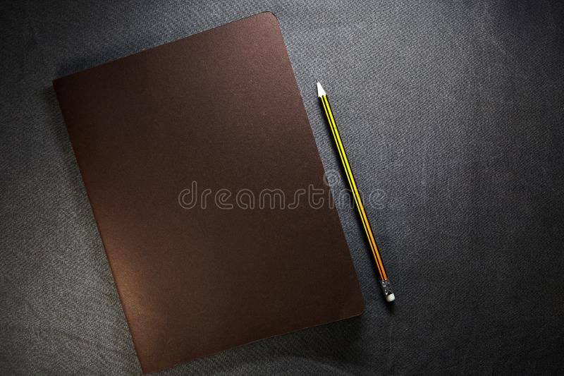 Open craft notepad with leather cover and a gray pencil on brown background stock images