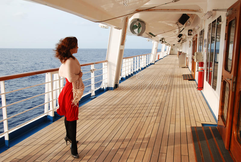On The Open Deck. The lady in red dress standing on a open deck of a cruise liner royalty free stock photography