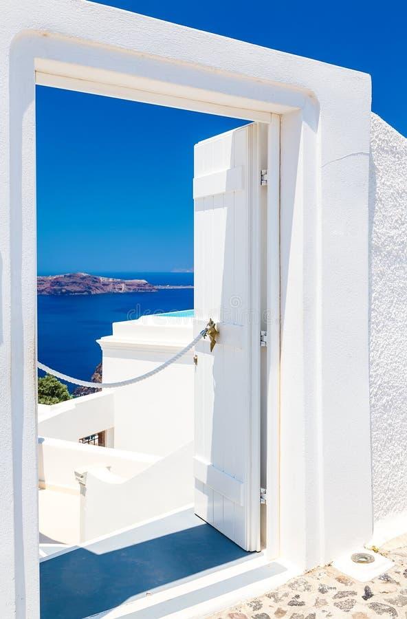 Open deur aan terras met lijst en stoel en mooie mening van overzees en bergen in Oia, op Santorini-eiland, Griekenland stock foto's