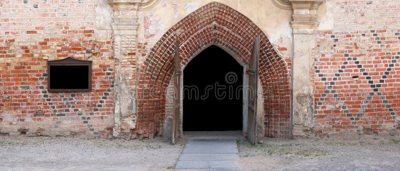 Open deuren aan de oude geruïneerde dorpskerk stock fotografie