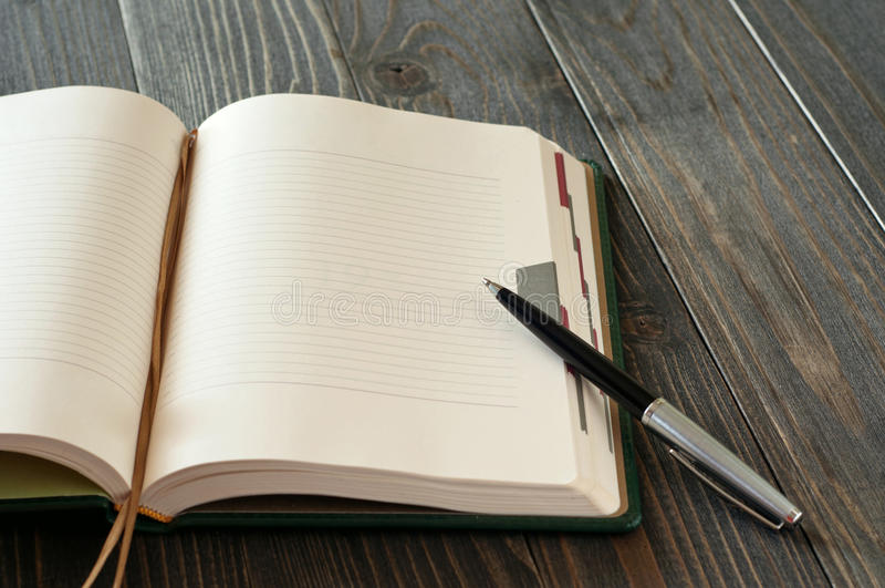 Open diary with blank pages and pen. Closeup on a dark wooden table royalty free stock images