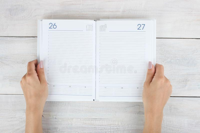 Open diary in hand. On wooden background. Concept planning royalty free stock images