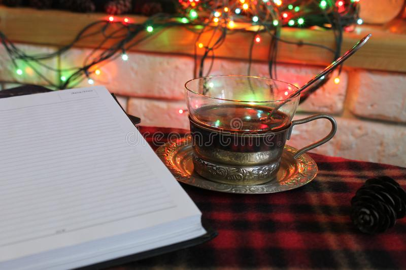 Open diary, transparent Cup of tea in a steel Cup holder on the background of a burning fireplace and Christmas garland royalty free stock photo
