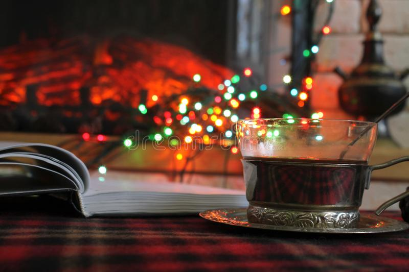 Open diary, transparent Cup of tea in a steel Cup holder on the background of a burning fireplace and Christmas garland royalty free stock image