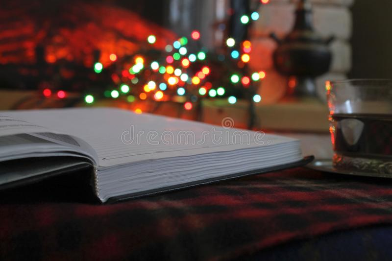 Open diary, transparent Cup of tea in a steel Cup holder on the background of a burning fireplace and Christmas garland royalty free stock photography