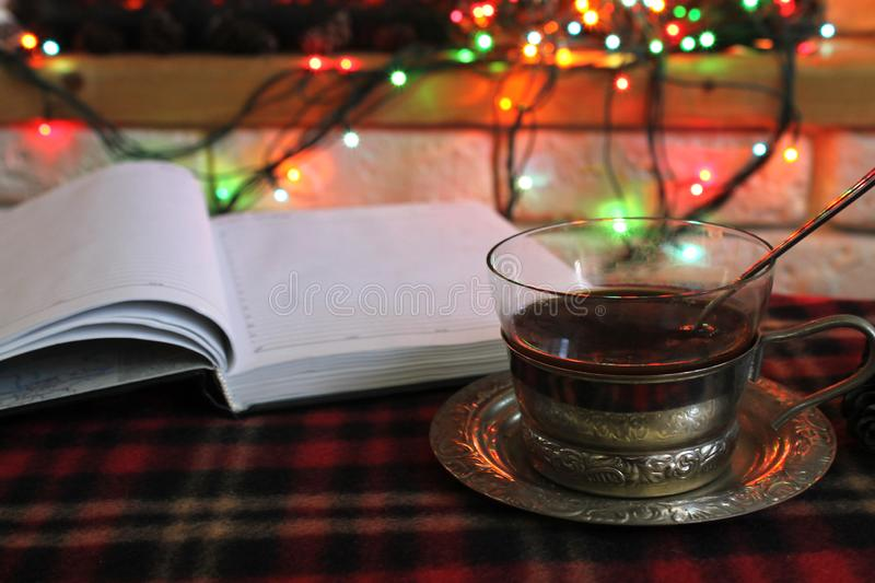 Open diary, transparent Cup of tea in a steel Cup holder on the background of a burning fireplace and Christmas garland royalty free stock images