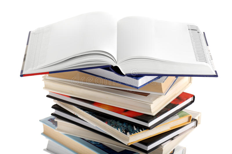 Open dictionary with blank pages on top of books. An opened dictionary with both pages blank, lying on top of a book stack, isolated on seamless white background stock images