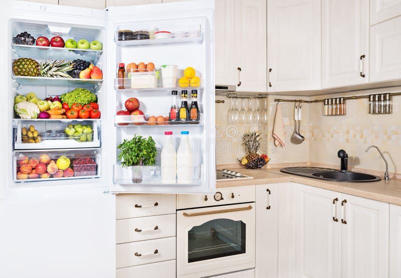 Open die ijskast met verse vruchten, groenten en melk wordt gevuld royalty-vrije stock foto