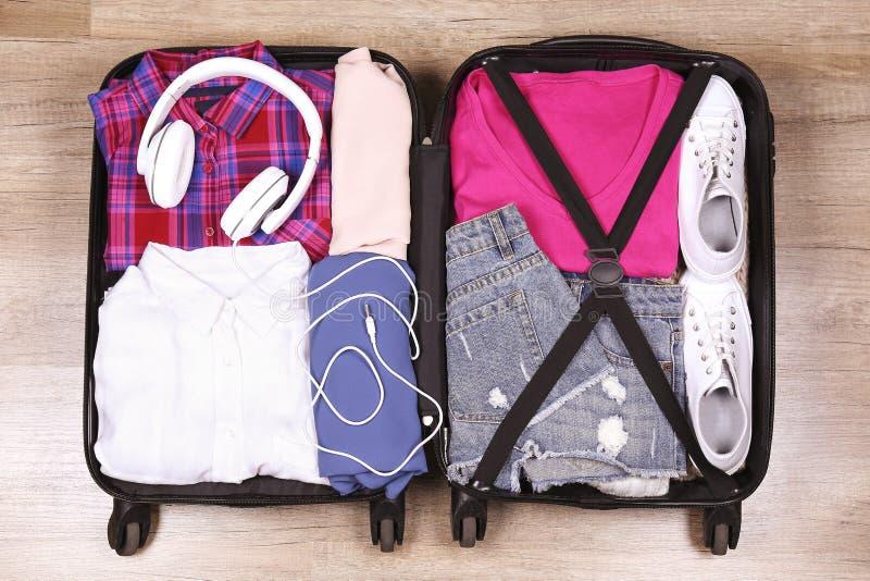 Open die kofferhoogtepunt met verschillende kleren wordt gestapeld stock afbeelding