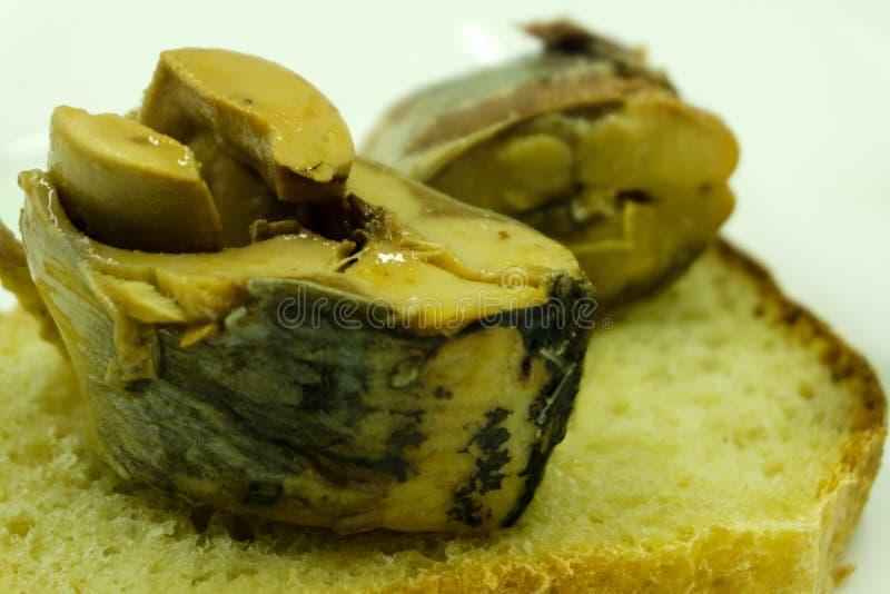Open die sandwich van bruine brood en plakken van filet van ingelegde Atlantische haringen op een schotel onder van één of andere stock afbeelding