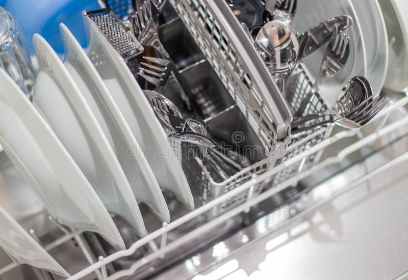 Open dishwasher with clean dishes stock image