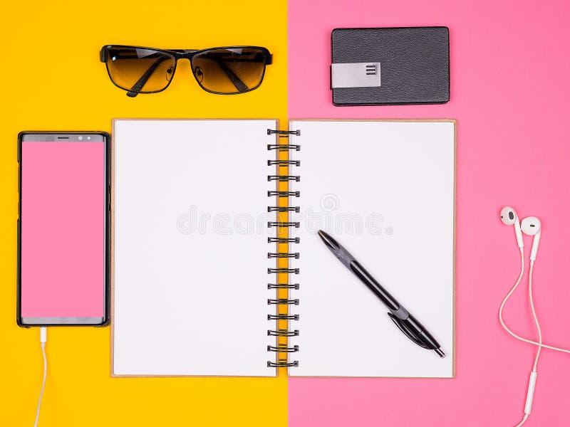 Open document notitieboekje naast een pen, zonnebril en smartphone met hoofdtelefoons op twee gekleurde achtergrond stock foto's