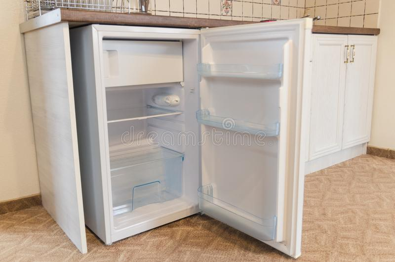 Open door of an empty fridge. An open door of an empty fridge or freezer close up view. Kitchen in the hotel room interiors concept. Shelves of the refrigerator royalty free stock photography