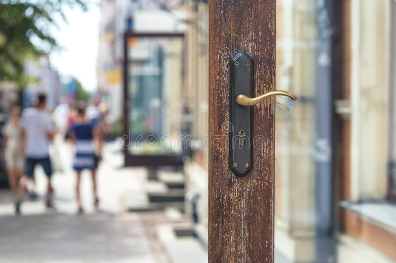 Open door of a store on a city street. Open wooden door with a lock on the background of a city street with pedestrians and cars on a summer day royalty free stock images