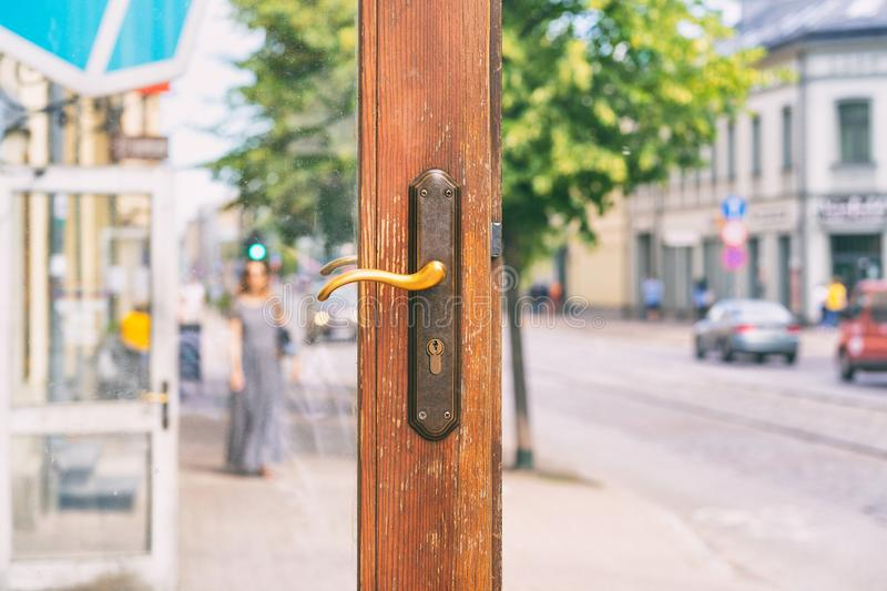 Open door of a store on a city street. Open wooden door with a lock on the background of a city street with pedestrians and cars on a summer day stock photos