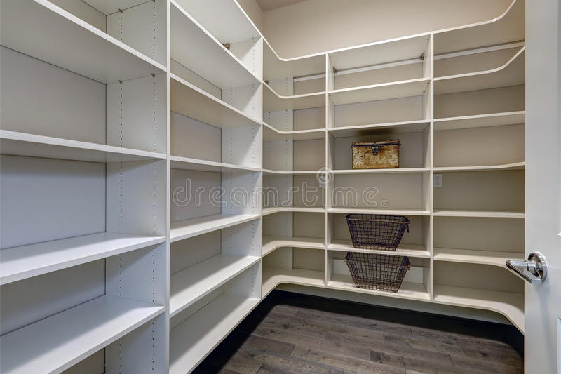 Open door to empty pantry room with white shelves royalty free stock images