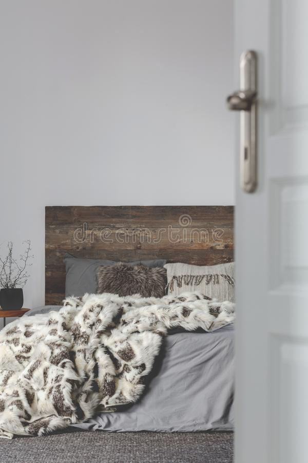 Open door to grey elegant bedroom interior with rustic design, copy space on empty wall. Open door to grey interior with rustic design, copy space on empty wall royalty free stock photography