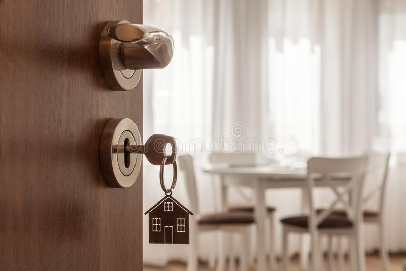 Open door to a new home. Door handle with key and home shaped keychain. Mortgage, investment, real estate, property and new home c stock image