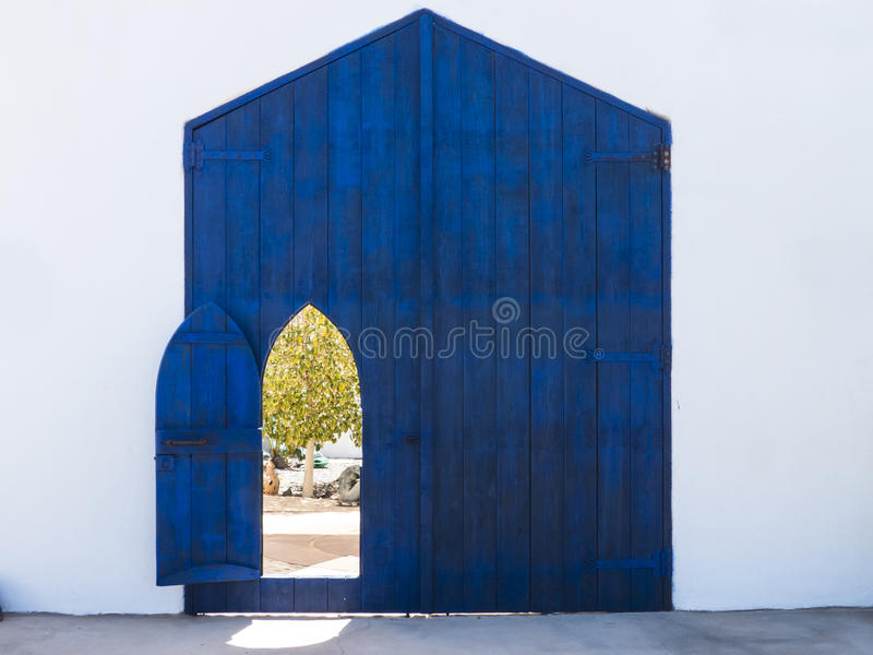 Open door to a patio with tree. A open door in a blue gate giving way to a patio with green tree royalty free stock image