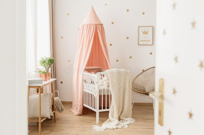 Open door to pink nursery. View through half open door on a white, minimalist crib in a pastel pink and gold nursery interior for a baby girl stock images