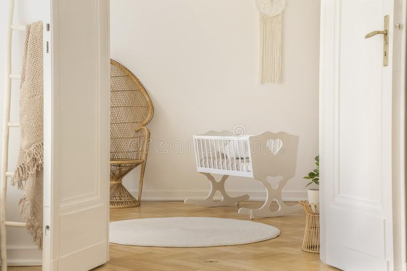 White scandi kid room with crib and wicker peacock, real photo. Open door to white scandi kid room with cradle and wicker peacock and carpet on the parquet, real royalty free stock images