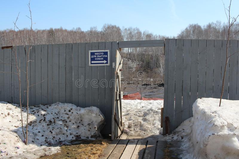 An open door in the wooden fence with a sign place for dogs of the city outskirts the village of Koltsovo in the winter. An open door in the wooden fence with a stock photo