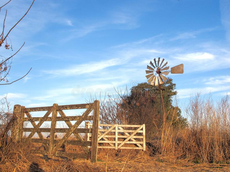 Agricultural field gates, the old windmill to extract water stock image