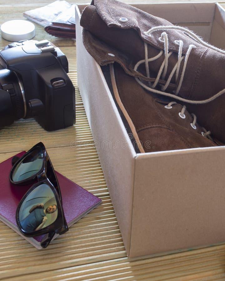 Open doos met een paar van laarzen en camera Mens die aan een avontuur voorbereidingen treffen royalty-vrije stock fotografie