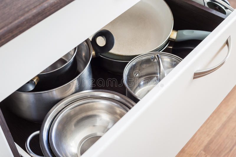 Open drawer of cabinet with steel pots and pans royalty free stock photo