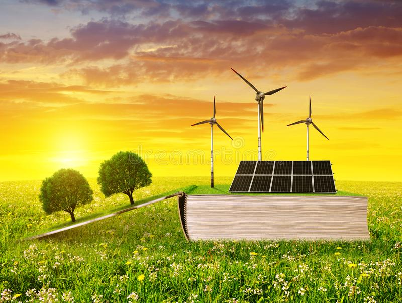 Open ecologisch boek met zonnepaneel en windturbine op weide bij zonsondergang stock afbeeldingen