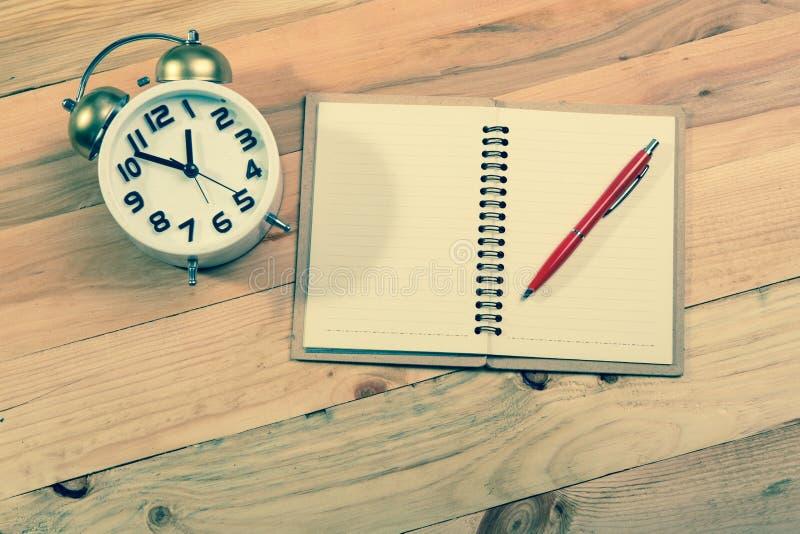 Open een lege witte notitieboekje, een pen en een wekker stock foto's