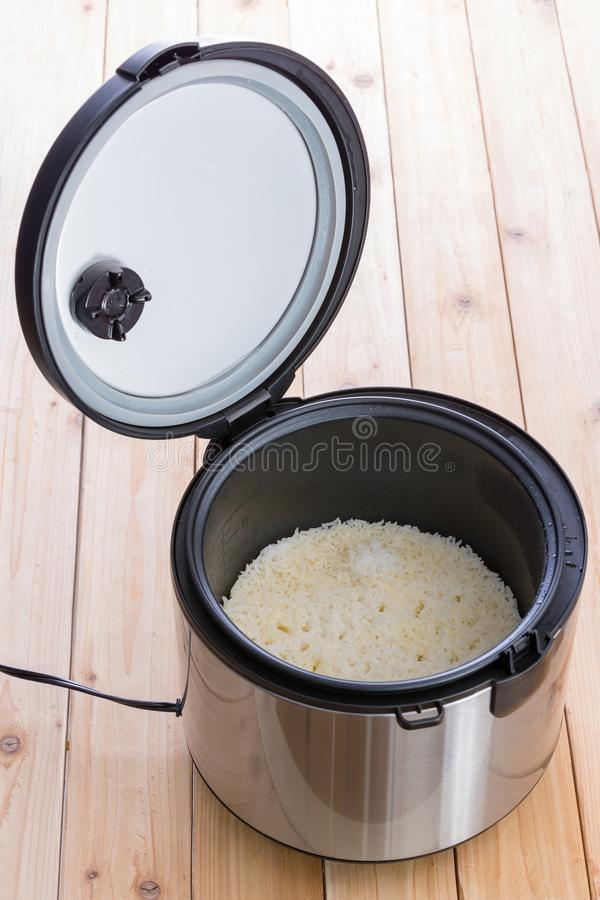 Open electric steamer pot with long grain rice stock photography