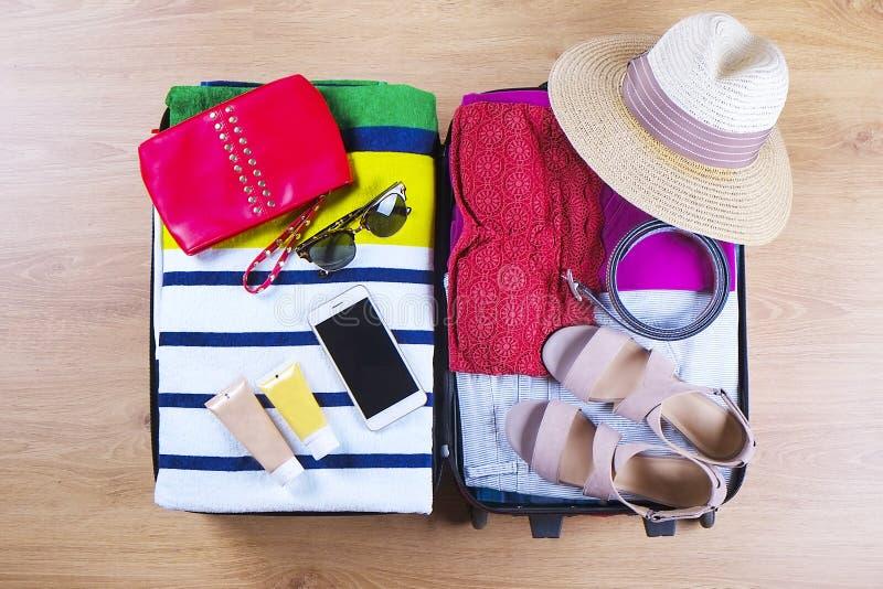 Open embalou a mala de viagem com roupa e acessórios fêmeas do verão, chapéu, óculos de sol, toalha de praia, proteção solar e ma imagens de stock