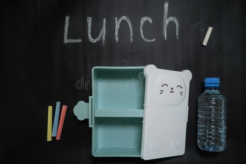 Open an empty lunch box with a sweet little face and a bottle of water on a black background with colorful crayons and lunch royalty free stock photo