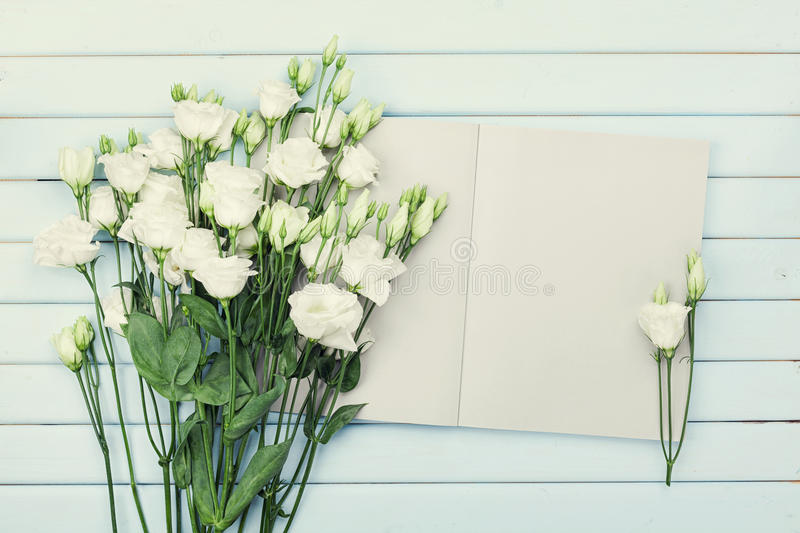 Open empty notebook and bouquet of white flowers eustoma on blue rustic table from above. Woman working desk. Flat lay styling. Open empty notebook and bouquet stock photo