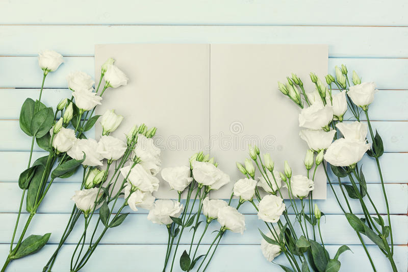 Open empty notebook and bouquet of white flowers eustoma on blue rustic table top view. Woman working desk. Flat lay. Open empty notebook and bouquet of white royalty free stock images