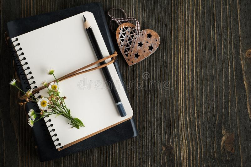 Empty notebook with wild flowers. Open empty notebook with wild flowers, heart and copy space stock images
