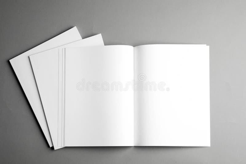 Open en gesloten lege brochures op grijze achtergrond, hoogste mening royalty-vrije stock afbeeldingen