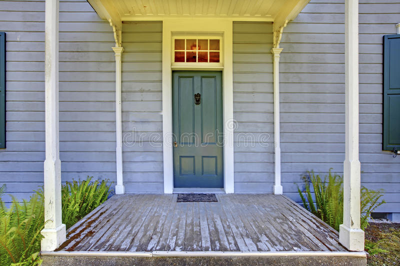 Open entrance porch with columns and blue door of an old house in Lakewood, WA. USA. Small open entrance porch with white columns and blue door of an old house stock images
