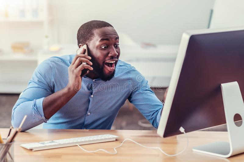 Open eyed African American man talking on phone royalty free stock image