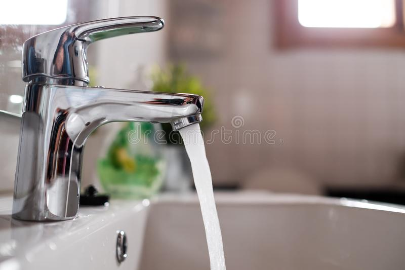 Open faucet washbasin with high water pressure stock photo