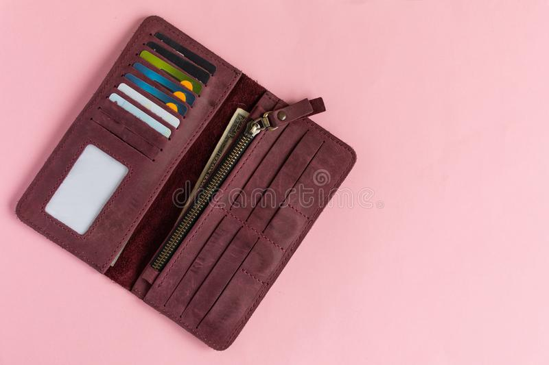 Open female wine-colored wallet with money and credit cards on pastel pink background royalty free stock photo