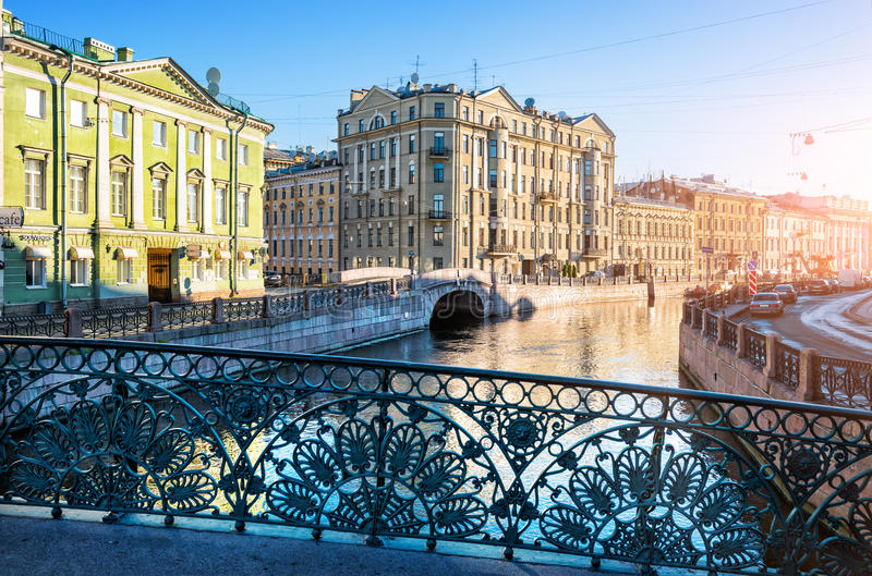The open fence of the Singers` Bridge. Across the Moika River in St. Petersburg in the early summer morning royalty free stock photos