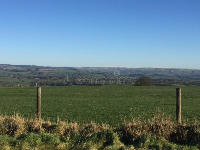 Open fields looking towards the Peak District. On a cloudless, sunny winter day. Small grass verge at the forefront with two wooden fence posts framing the stock photos