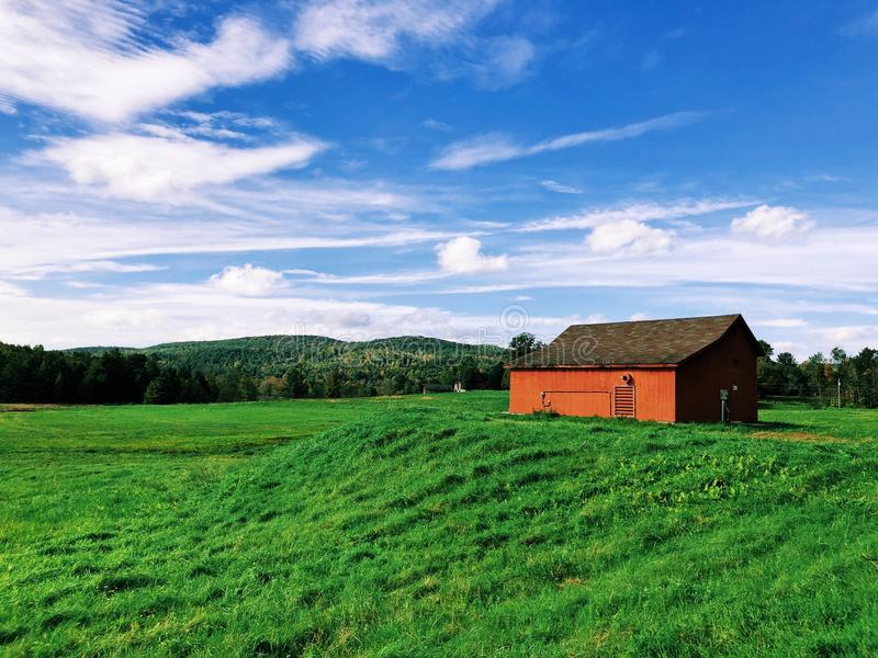 Open filed in the summer with a red barn stock photos