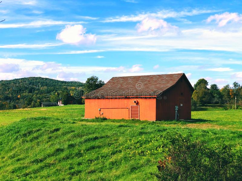 Open filed in the summer with a red barn stock photo