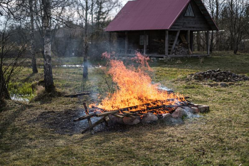 Open fire burning in countryside home garden. Controlled pyromaniac stock image
