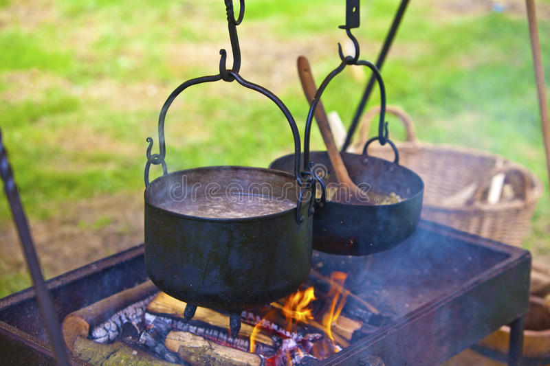 Open fire cooking. Cooking meal outdoors with pots on an open fire stock image