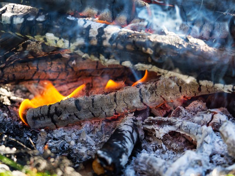 Open fire with hot ash and charcoal burning with bright orange flame, close up royalty free stock photography